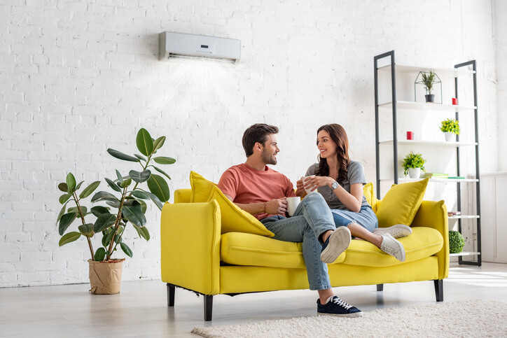 A happy couple laughing and drinking coffee on a bright yellow couch in a white room with a ductless AC unit on the wall.