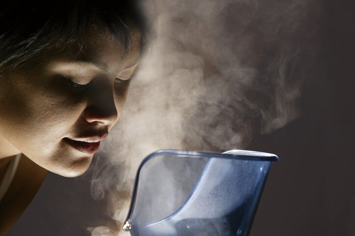 A woman breaths in the steam rising from a humidifier.