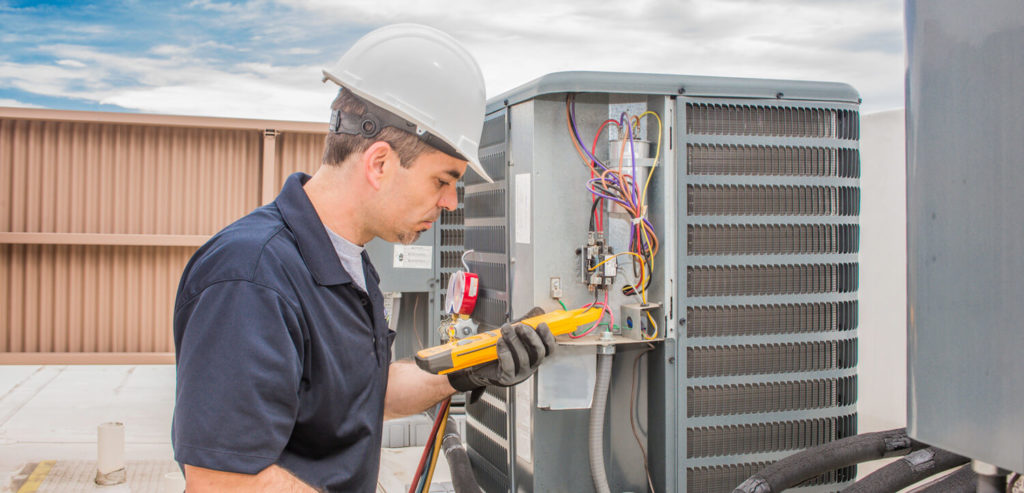 hvac technician working on rooftop unit
